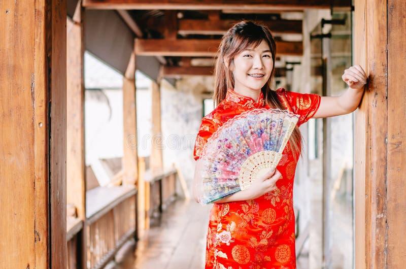Portret młodej kobiety uśmiechu odzieży piękny cheongsam głęboki - czerwieni smokingowy mienie fan przyglądająca kamera Gody i św zdjęcie royalty free