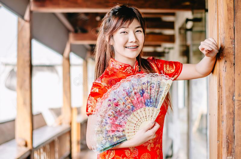 Portret młodej kobiety uśmiechu odzieży piękny cheongsam głęboki - czerwieni smokingowy mienie fan przyglądająca kamera Gody i św obraz royalty free