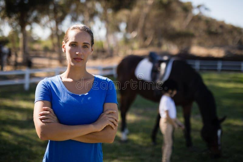 Portret młody żeński dżokej z siostrą koniem w tle fotografia stock