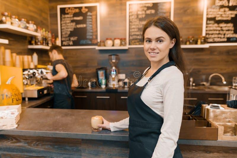 Portret młody żeński małego biznesu właściciel - mały nowożytny sklep z kawą, ufna kobiety pozycja przy kontuarem z barista wor zdjęcie stock