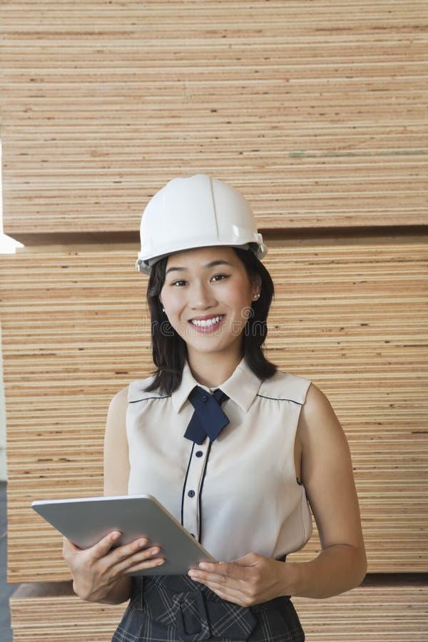 Portret młody żeński przemysłowy pracownik używa pastylka peceta z drewnianymi deskami w tle obraz royalty free
