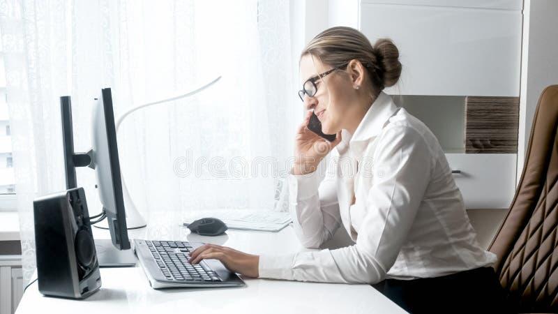 Portret młody żeński szefa obsiadanie za biurkiem i opowiadać telefonem obrazy royalty free