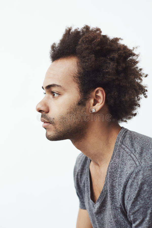 Portret młody afrykański mężczyzna w profilu nad białym tłem zdjęcia stock