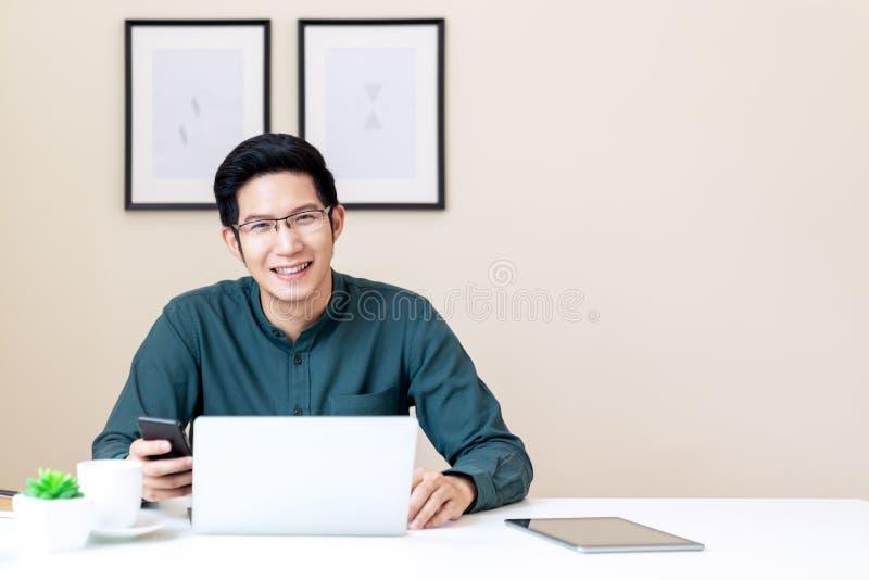 Portret młody atrakcyjny azjatykci biznesmen lub studencki używa telefon komórkowy, laptop, pastylka, pije kawowego obsiadanie na obraz royalty free