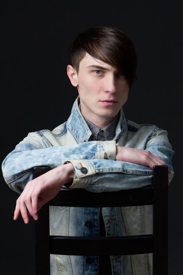 Portret młody atrakcyjny faceta obsiadanie na krześle obrazy stock
