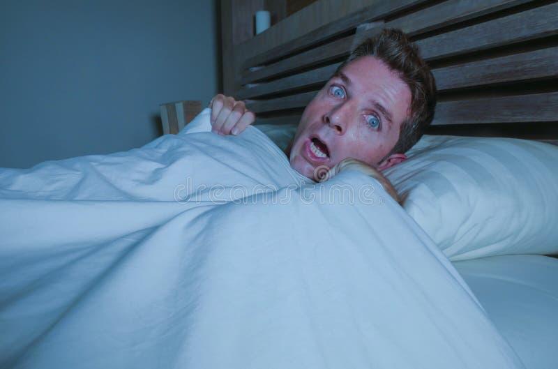 Portret młody atrakcyjny okaleczający mężczyzna w strachu i paniki cierpienia horroru koszmarze budzi się up nagle przy nocy lyin fotografia royalty free