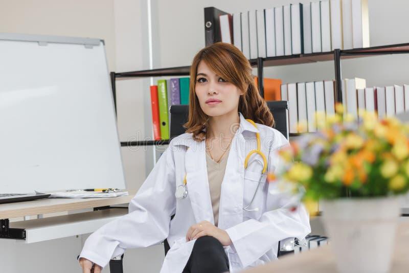 Portret młody Azjatycki kobiety lekarki obsiadanie na miejscu pracy szpitalny biuro zdjęcie royalty free
