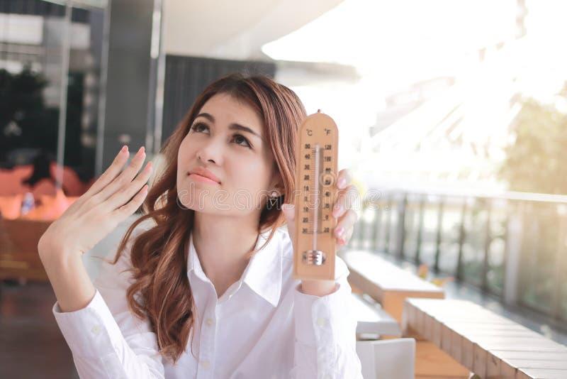 Portret młody Azjatycki kobiety mienia termometr i uczucie w ten sposób gorący z wysokotemperaturowym na biurku przeciw światło s obraz royalty free