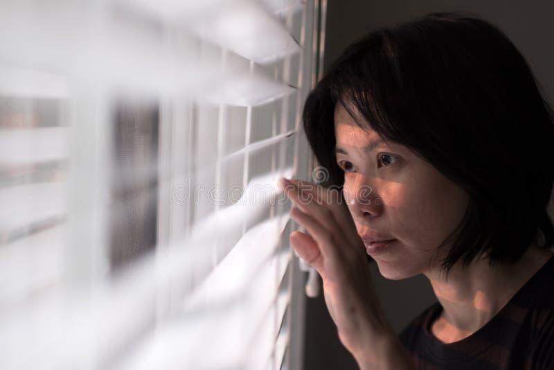 Portret młody Azjatycki kobiety zerkanie z okno zdjęcia stock