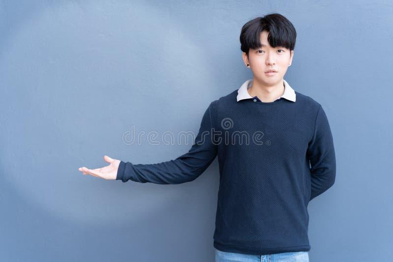 Portret Młody Azjatycki nastoletni chłodno włosiany elegancki jest ubranym błękitny pulower wskazuje głównej atrakcji pustą przes obrazy stock