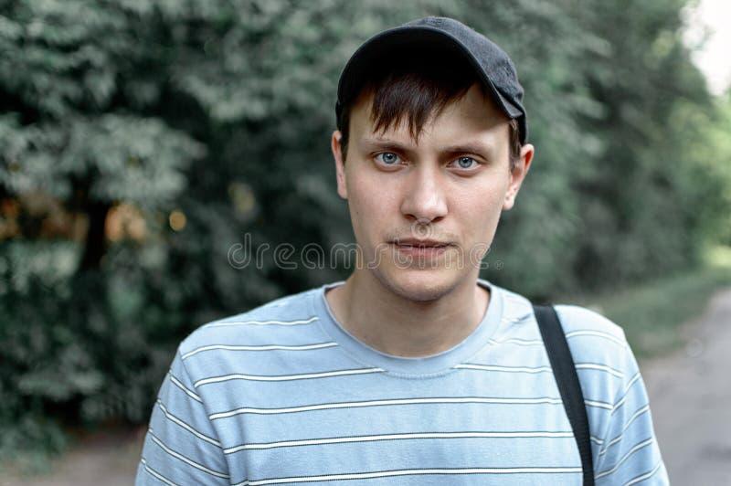 Portret młody błękit przyglądał się mężczyzna w parku obraz stock