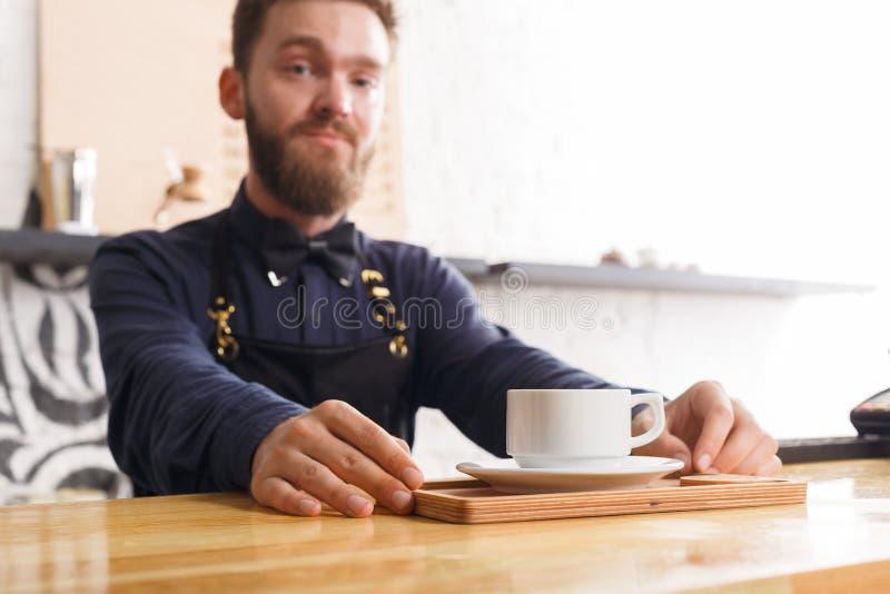Portret młody barman przy sklep z kawą kontuarem zdjęcia stock