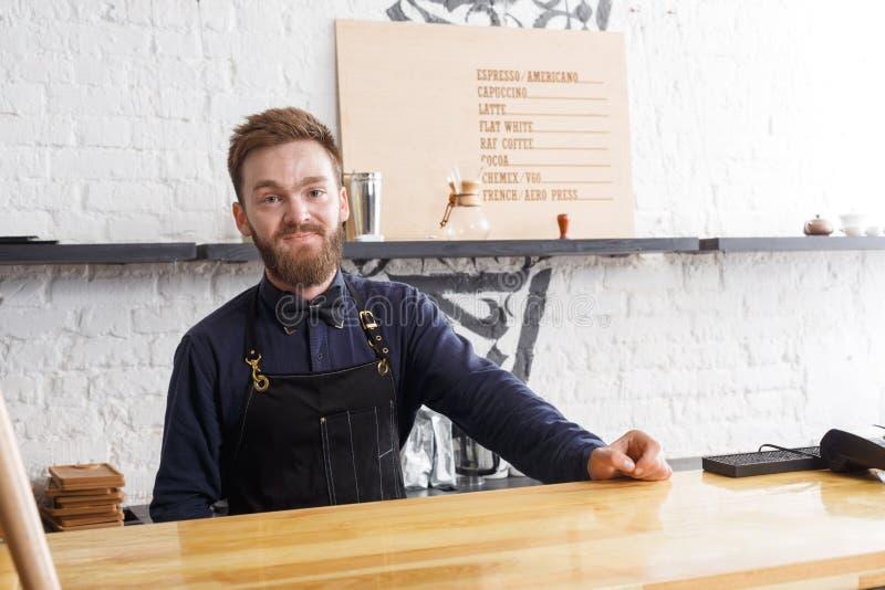 Portret młody barman przy sklep z kawą kontuarem obraz stock