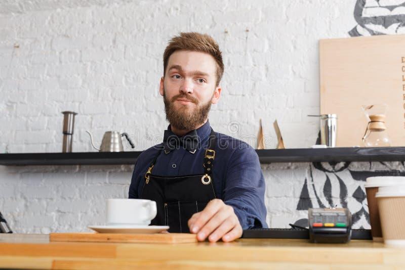 Portret młody barman przy sklep z kawą kontuarem zdjęcie royalty free