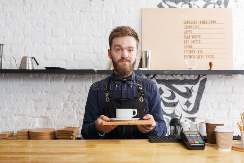Portret młody barman przy sklep z kawą kontuarem zdjęcia royalty free