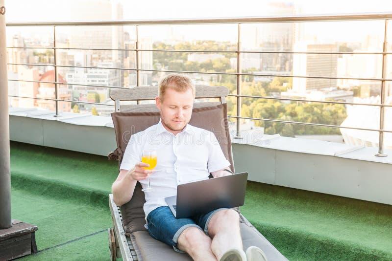 Portret Młody biznesmen swobodnie siedzi na deckchair na biuro tarasie z Miastowym krajobrazem z napojem pracuje na laptopie zdjęcia stock
