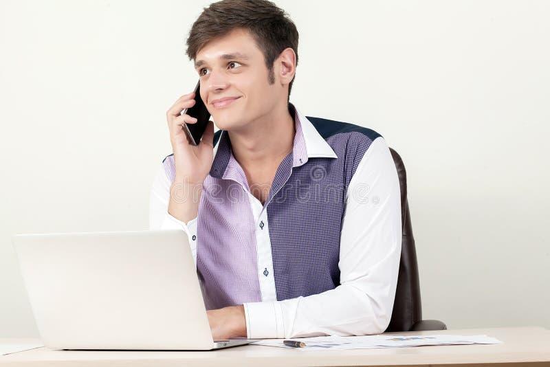Portret młody biznesmen używa telefon komórkowego, laptop przy w pieniężnym raporcie i podczas gdy siedzący obraz royalty free