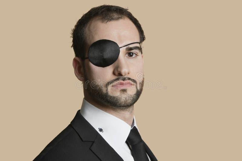Portret młody biznesmen z oko łatą nad barwionym tłem zdjęcia royalty free