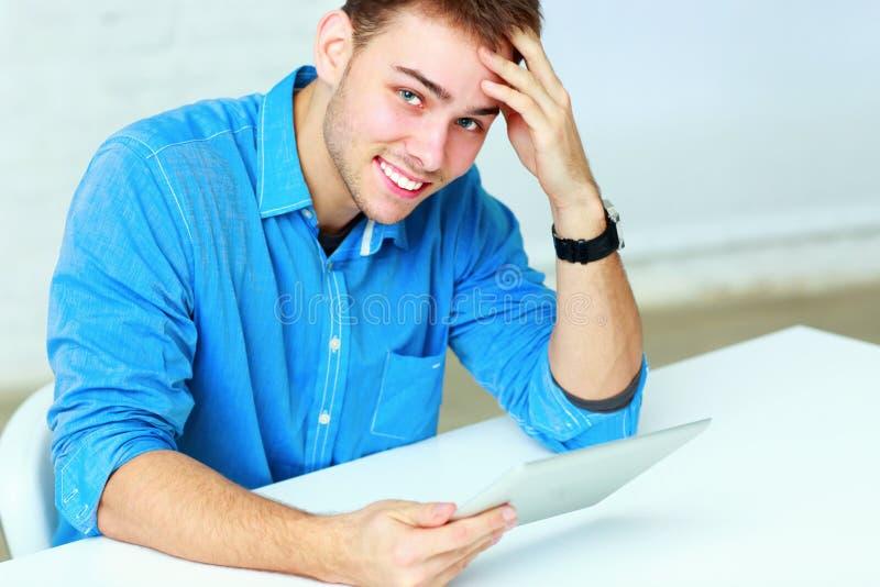 Portret młody biznesmena mienia pastylki komputer i patrzeć kamerę zdjęcia royalty free