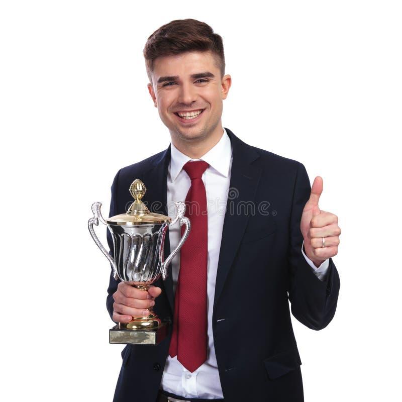 Portret młody biznesmena mienia trofeum i robić ok znakowi zdjęcia stock