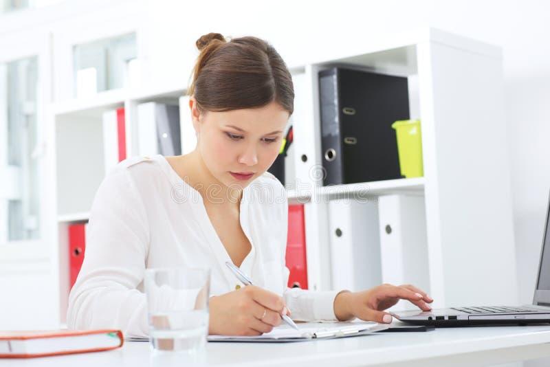 Portret młody bizneswoman z laptopem pisze na dokumencie przy jej biurem obraz stock