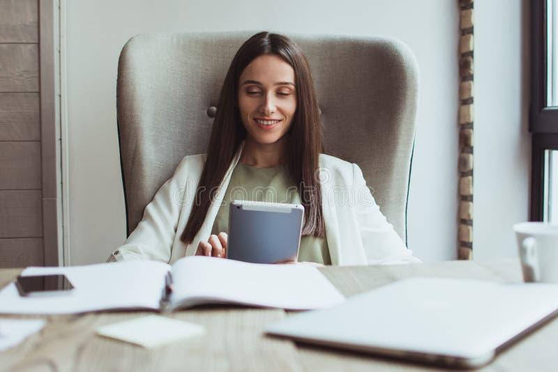 Portret młody bizneswomanu obsiadanie z jej laptopem w biurze obrazy royalty free