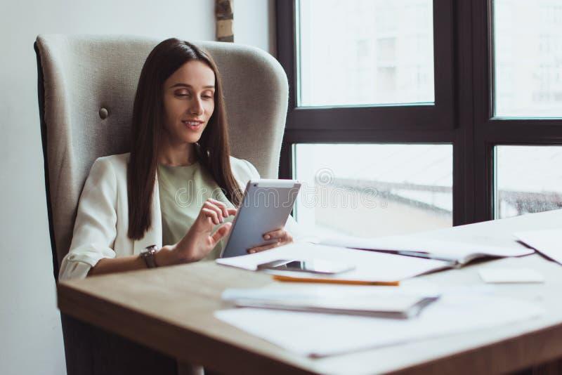 Portret młody bizneswomanu obsiadanie z jej laptopem w biurze zdjęcia stock