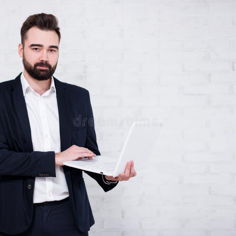Portret młody brodaty biznesmen używa komputer nad białym ściany z cegieł tłem fotografia royalty free