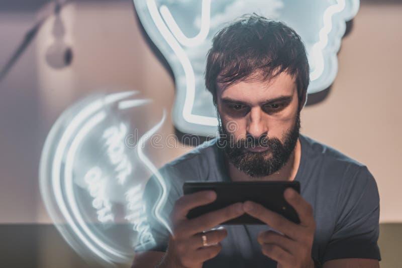 Portret Młody brodaty mężczyzna obsiadanie w ręka telefonie komórkowym i pisać na maszynie ekranie kawiarni i mienia horyzontalny fotografia stock