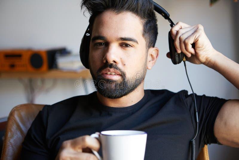Portret młody brodaty mężczyzna słucha muzyka w domu i pije kawę w hełmofonach Relaksujący i spoczynkowy czas zdjęcie stock