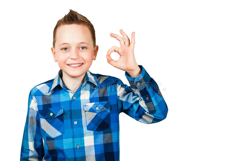 Portret młody chłopiec śmiech i pokazuje OK znaka na białym odosobnionym tle zdjęcia stock