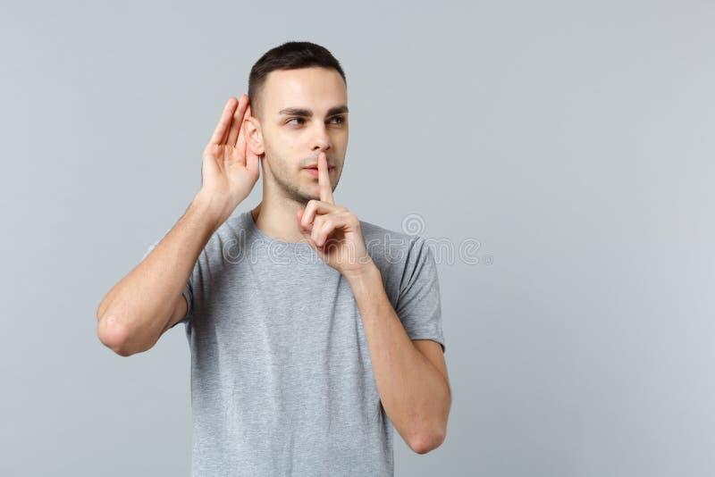 Portret młody człowiek podsłuchuje z przesłuchanie gestem, mówić był spokojny z palcem na warga gescie odizolowywającym dalej uci zdjęcie stock