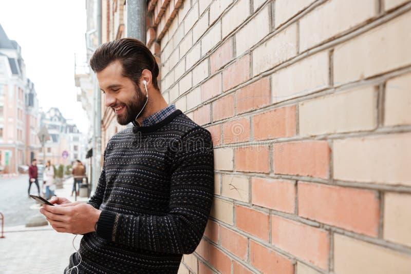 Portret młody człowiek słucha muzyka w pulowerze zdjęcia royalty free