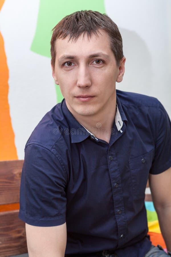 Portret młody człowiek w błękicie sleeved koszula, jeden osoby siedzieć salowy fotografia stock