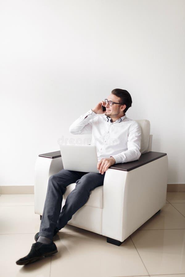 Portret młody człowiek W szkłach Używać telefonu komórkowego obsiadania krzesła Podczas gdy laptop Przeciw biały tłu obrazy stock