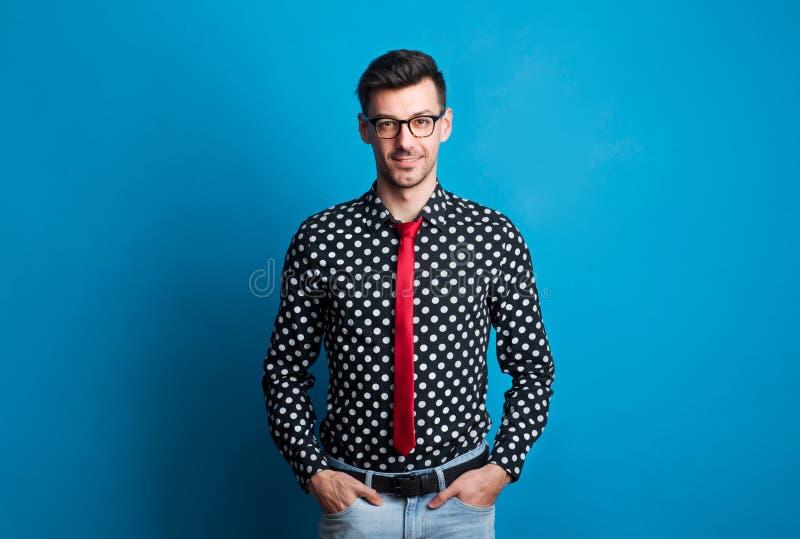 Portret młody człowiek z szkłami w studiu na błękitnym tle zdjęcie stock