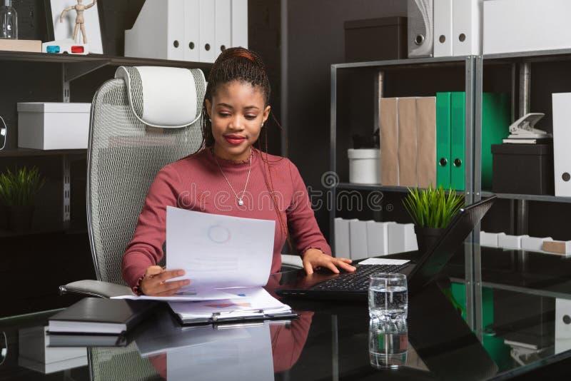 Portret młody czarny bizneswoman pracuje z mapami i diagramami przy biurkiem w biurze obrazy stock