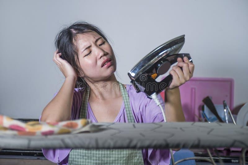 Portret młody dosyć zaakcentowany i sfrustowany Azjatycki Koreański kobiety mienia żelazo pracuje w domu kuchennych prasowań ubra obraz stock