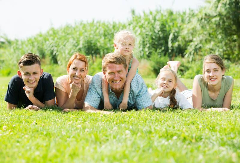 Portret młody dużej rodziny lying on the beach na zielonym gazonie outdoors fotografia royalty free