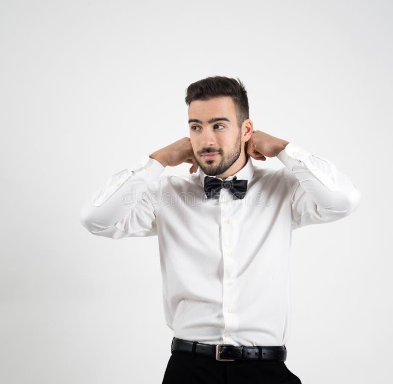 Portret młody elegancki luksusowy mężczyzna przystosowywa łęku krawat patrzeje daleko od obraz stock
