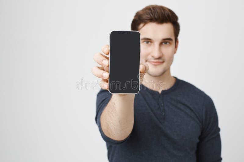 Portret młody europejczyka model reklamuje nowego smartphone, pokazywać je kamera, stoi nad szarym tłem sklep zdjęcia stock