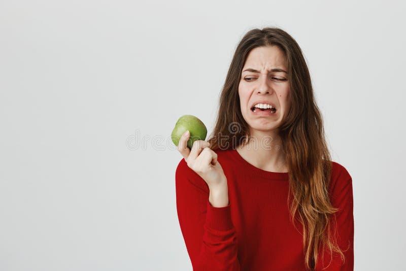 Portret młody europejski nastolatek wyraża obmierzłości mienia zieleni jabłka, odizolowywający nad białym tłem Ludzie mówją zdjęcie royalty free