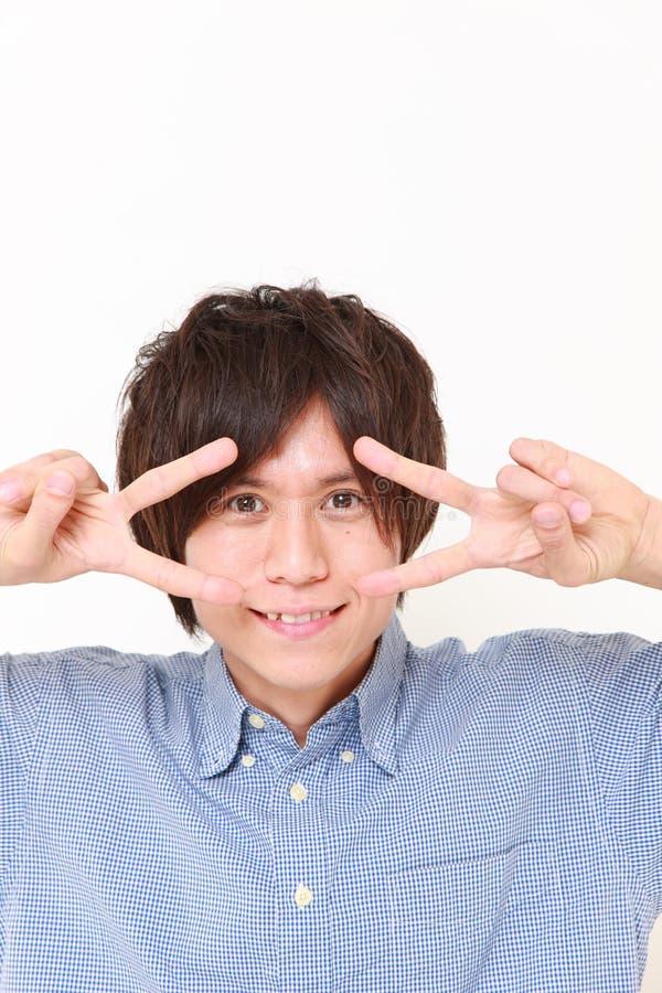 Portret młody Japoński mężczyzna pokazuje zwycięstwo znaka obraz stock