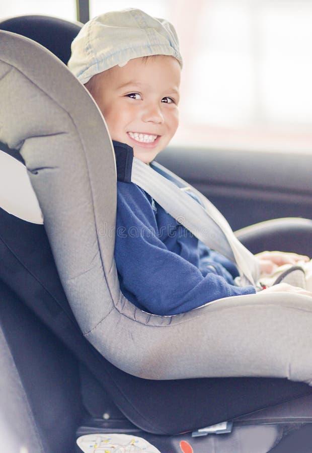 Portret Młody Kaukaski szczęśliwy Little Boy obsiadanie na samochód Sa fotografia stock