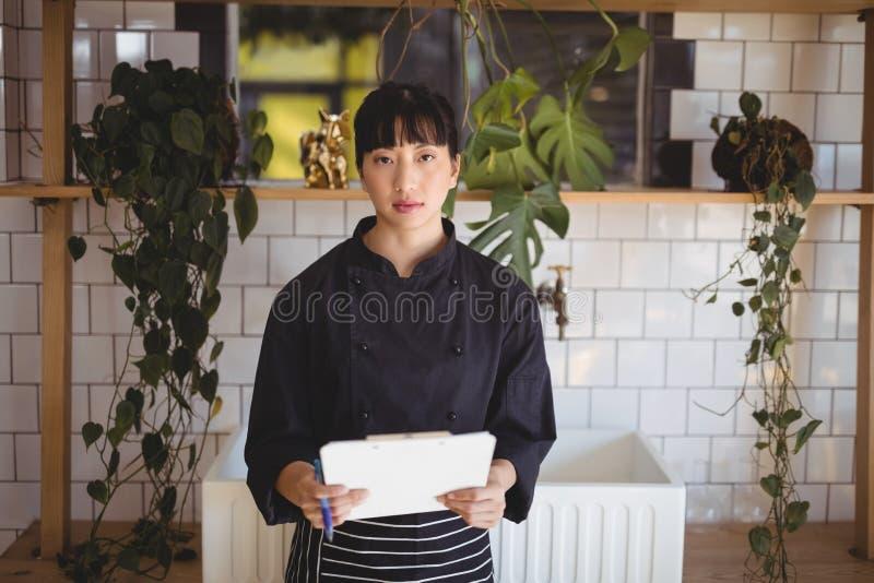 Portret młody kelnerki mienia schowek przeciw półce zdjęcia stock