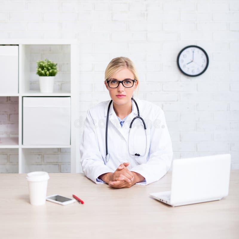 Portret młody kobiety lekarki obsiadanie w biurze obraz stock