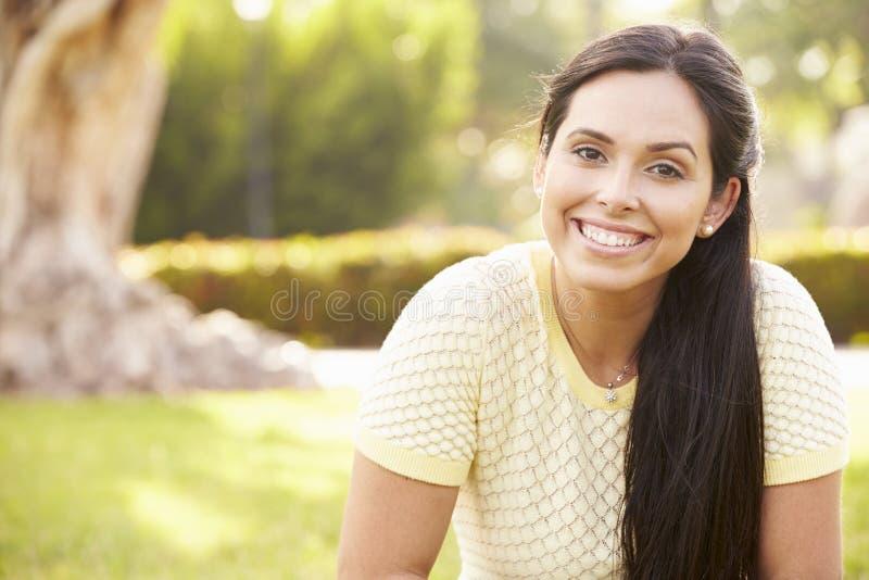 Portret Młody Latynoski kobiety obsiadanie W parku fotografia royalty free