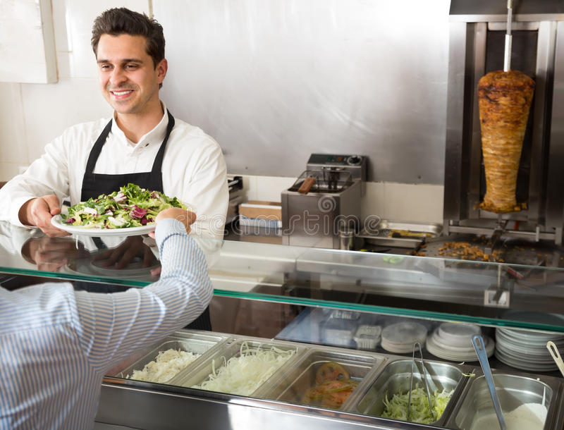 Portret młody męski fasta food pracownik przy kontuarem fotografia royalty free