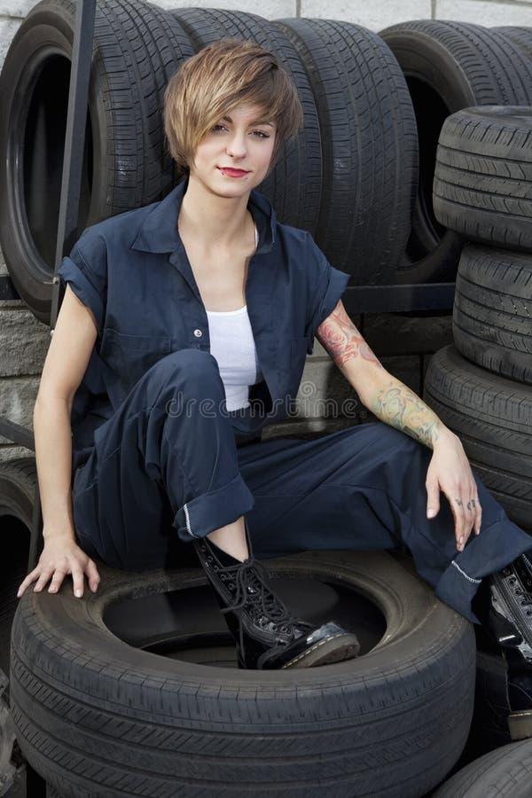 Portret młody mechanika obsiadanie na oponach w samochodowym warsztacie zdjęcia royalty free
