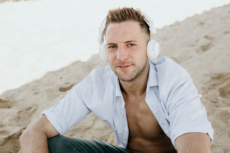 Portret Młody modnisia mężczyzna słucha muzyka w hełmofonach na smartphone w białej koszula i cajgach i siedzi obraz royalty free